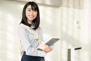 iPadを持ちながら笑顔でこちらを見る20代OL女性の写真素材 [FYI01227294]