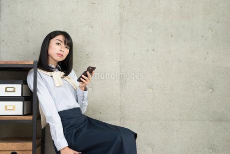 iPhoneを操作しながら棚に寄り掛かかる20代OL女性の写真素材 [FYI01227299]