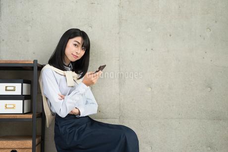 iPhoneを操作中の20代OL女性の写真素材 [FYI01227300]