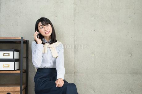 iPhoneで通話中の20代OL女性の写真素材 [FYI01227301]